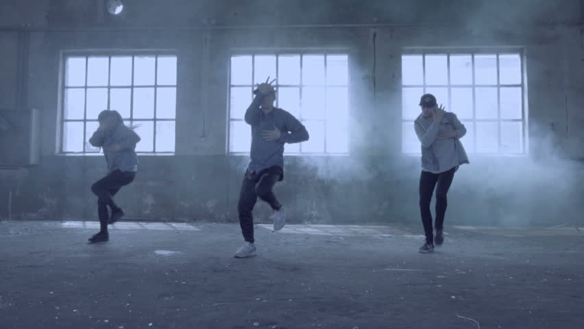 Video of active young group dancing choreography in an abandoned building with smoky background.