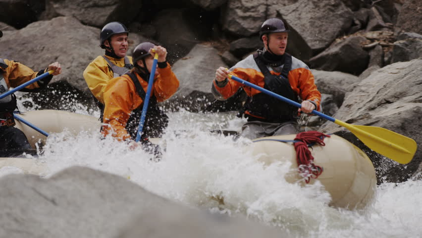 Whitewater rafting team descending raging rapids in Glenwood Canyon Colorado with paddles splashing in water tight panning shot in slow motion 4K