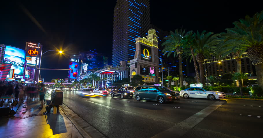 Las Vegas, Nevada, USA - traffic on illuminated Las Vegas Strip in front of the Bellagio Resort & Casino with Aria and Planet Hollywood at night - Timelapse without motion