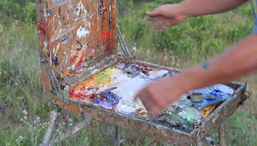 Portable easel, with telescopic legs and built-in paint box and palette. Closing the box   Shutterstock HD Video #17437855