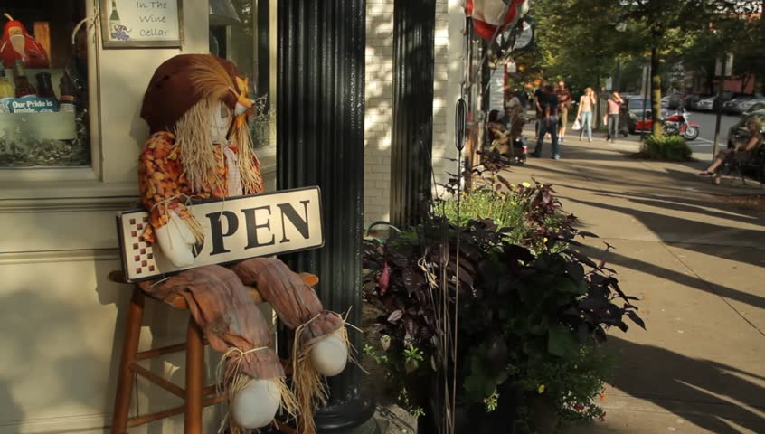 "COOPERSTOWN, NY - SEPT 24, 2011: A scarecrow holds an ""Open"" sign outside a main shop on September 24, 2011 in Cooperstown."