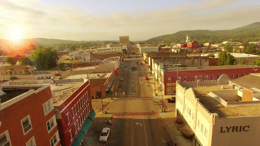 Aerial of small town America at sunrise on main street. Small town in Alabama at sunrise. Drone flying over making street in small town America. Urban scene over main street morning.
