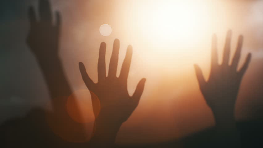 Silhouettes of hands raised in worship with light rays and Cross.