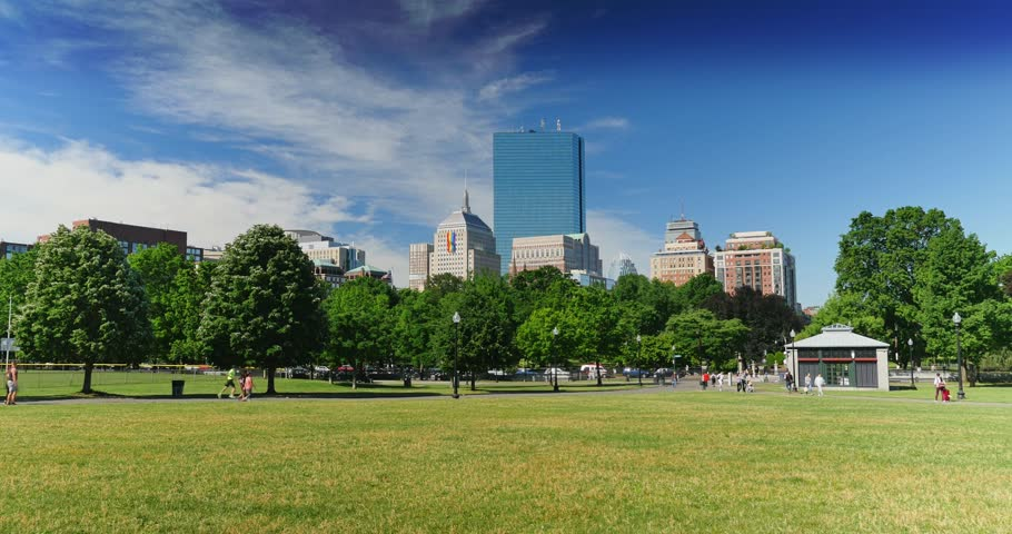 BOSTON, MA - Circa June, 2016 - A summer daytime establishing shot of people enjoying Boston Common Park.	A large rainbow flag is hanging from the John Hancock Building for Gay Pride Month.