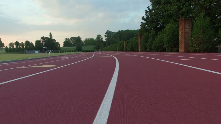 Low flying aerial around running track. Empty college running track at sunrise. POV fling over track on university campus.
