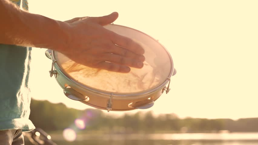 Musical instrument tambourine or pandeiro on a background of the sky at sunset | Shutterstock HD Video #17480950