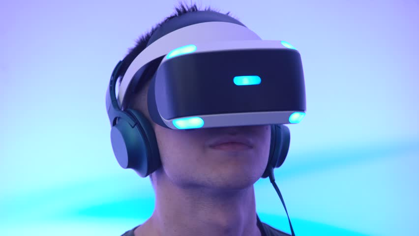 MOSCOW, RUSSIA - JUNE 19, 2016: A young man uses VR-headset display and headphones for virtual reality game on the Geek Picnic - festival about technology, art and science.