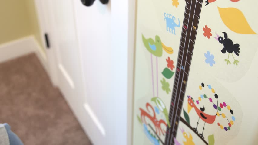 A dad measures his preschool aged soon against a wall decal to see how tall he is