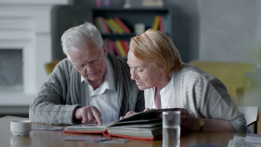 elderly happy couple spend time together and nostalgic. they looking old photo album and smiling #17493541