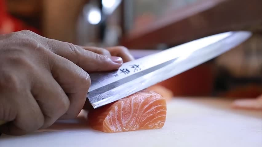 Sushi Chef Slices fresh Salmon on the sushi bar.  A sushi-man slicing a salmon steak with his Japanese knife. Preparing sushi nigiri fish. Japanese cuisine recipes.
