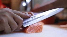 Sushi Chef Slices fresh Salmon on the sushi bar.  A sushi-man slicing a salmon steak with his Japanese knife. Preparing sushi nigiri fish. Japanese cuisine recipes.