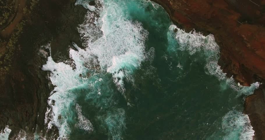 AERIAL: epic ocena overhead view. Bird's-eye view at coastline with green waves crashing.