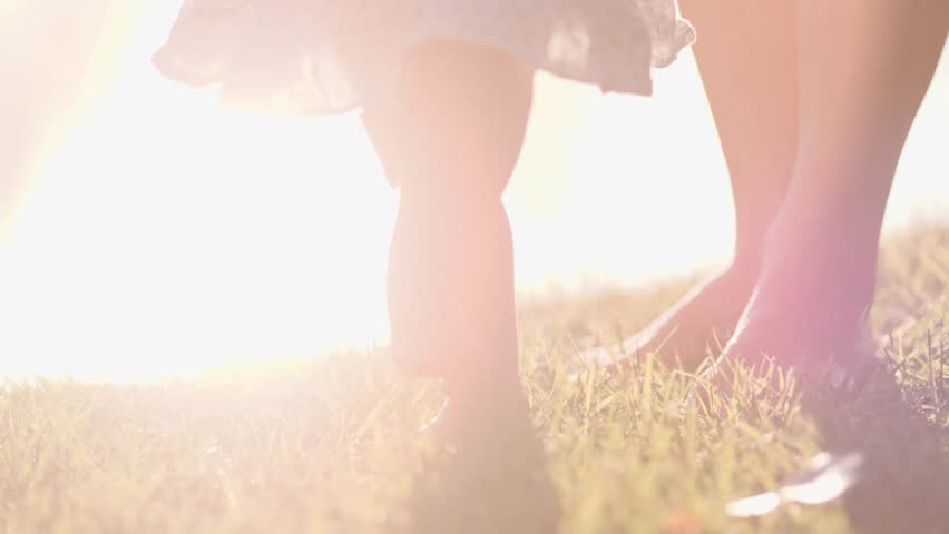 Little baby learns to walk. First Steps. Slow Motion 120 fps, 4K. Mother is teaching her child to do the first steps on a green grass in summer. Close up on feet. Happy childhood and Maternity. Family #17520448