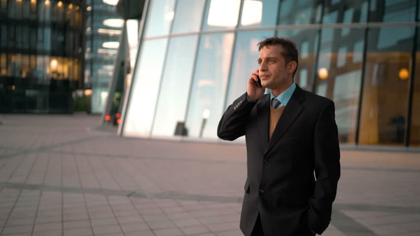 Young successful european businessman treating coffee cup his friend with tablet PC. Smile conversation. Men going work together. Glass business centre building at the bg. Teal and Orange style #17520481