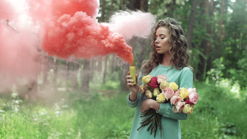 Beautiful girl in a forest with a color smoke grenade, slow motion