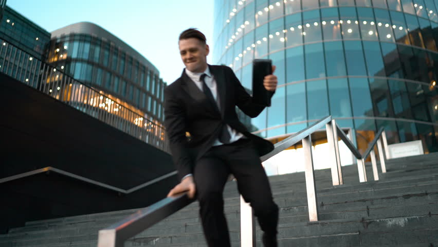 Young successful businessman easy slide on the outdoor stairs rail with smile and jump at the end. Glass business centre building at the background. Teal and Orange style. Wide Ultra HD tripod shot.