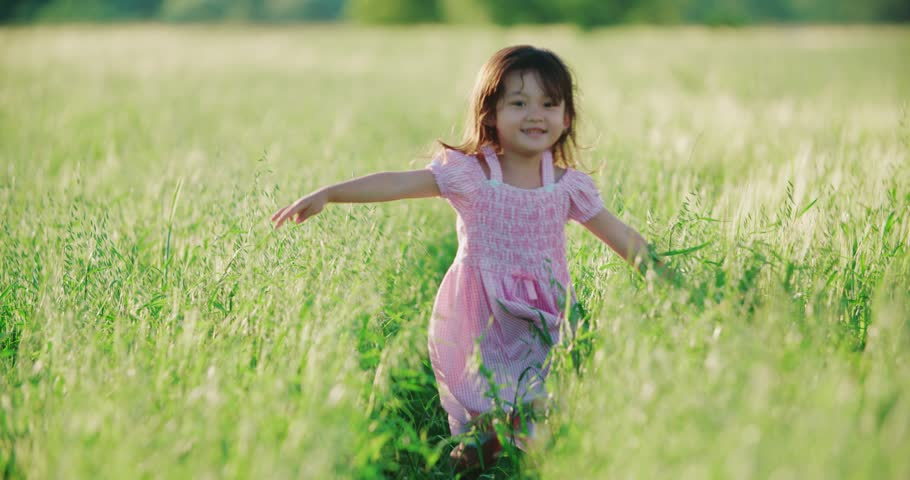 Little Asian girl running in a green field of young wheat, flowing hair,slow motion