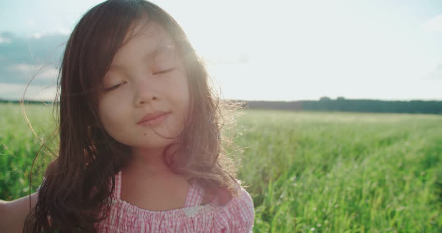 little Asian girl standing in a green field of young wheat,close-up, flowing hair,slow motion,sunset Royalty-Free Stock Footage #17568448