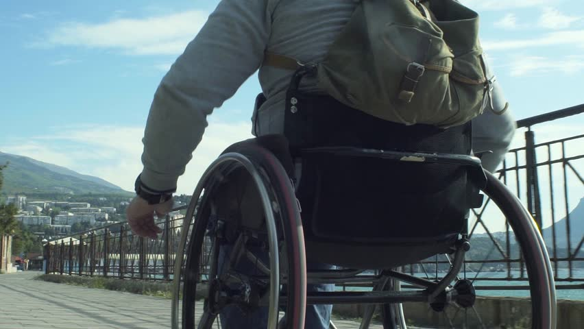 Slow motion shot of a traveling man with a backpack in wheelchair walking on the embankment along the sea