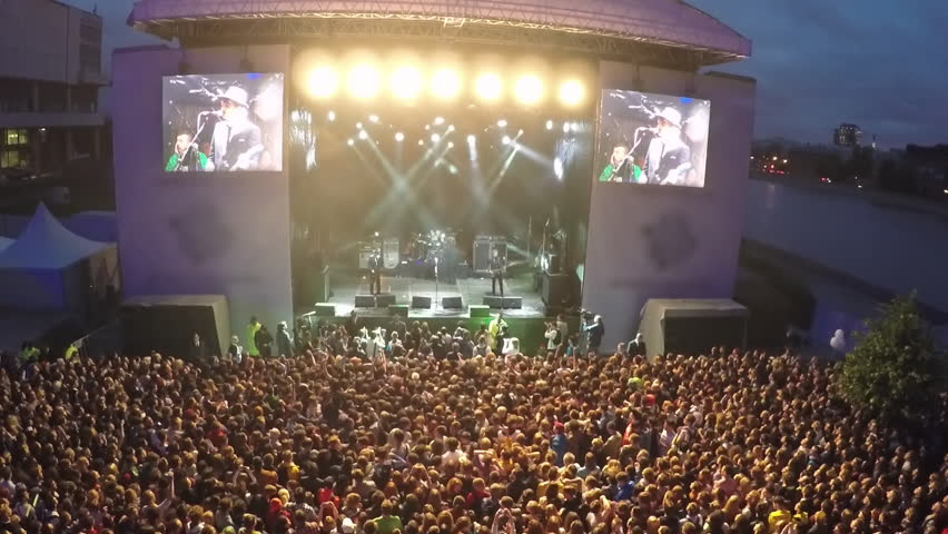 Aerial show of unidentified musicians on the stage and excited audience. Crowd of people enjoying night outdoor rock concert