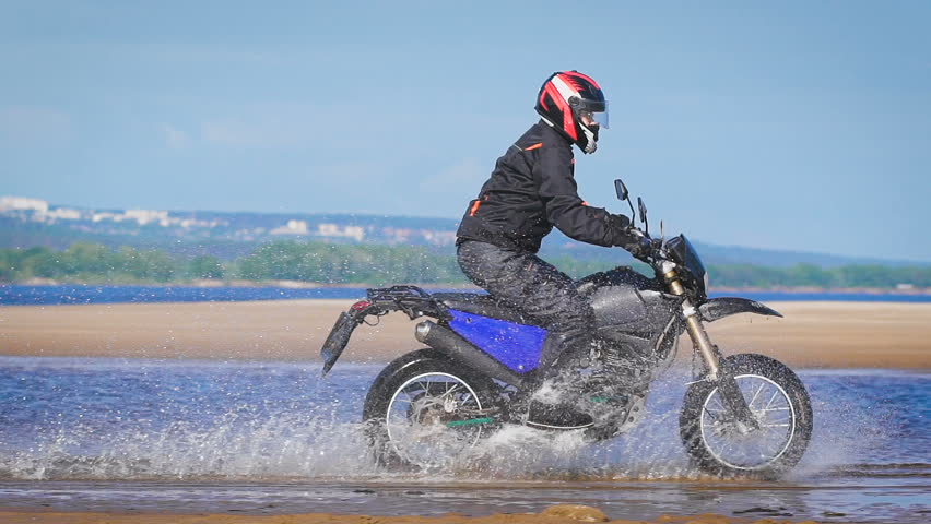 Extreme driving a motorcycle. A skilled biker riding on the edge of water | Shutterstock HD Video #17615179