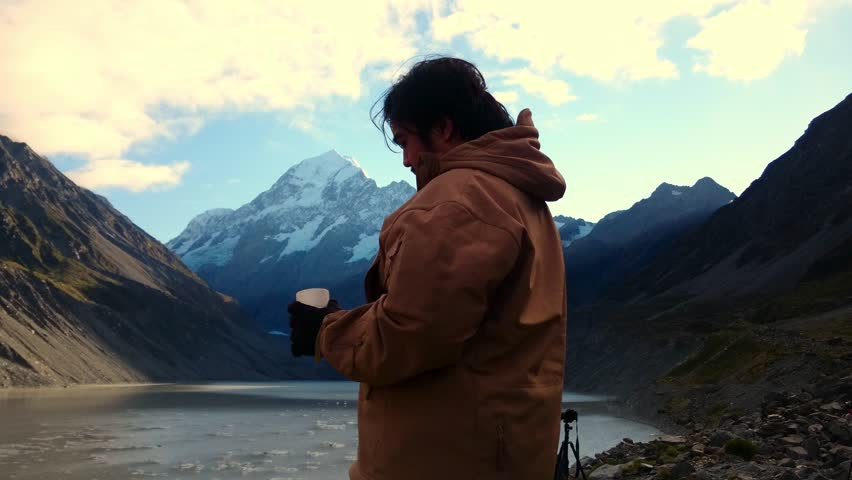 Man Drinking From Thermos While Enjoying The Scenery at Hooker Lake Glacier Terminal, Mount Cook National Park, New Zealand. Camera Slide Left | Shutterstock HD Video #17638309