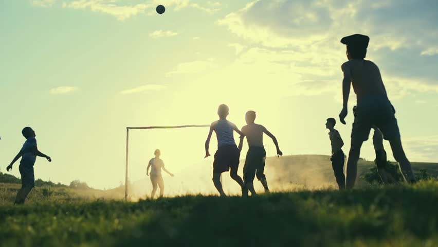 Football in his native village. Group of young guys playing football on the background of sunset. Slow motion.
