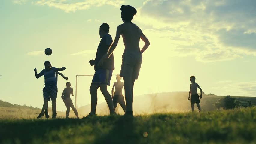 Boys are playing football in the sunshine day. Happy childhood and football in the village. Slow motion.