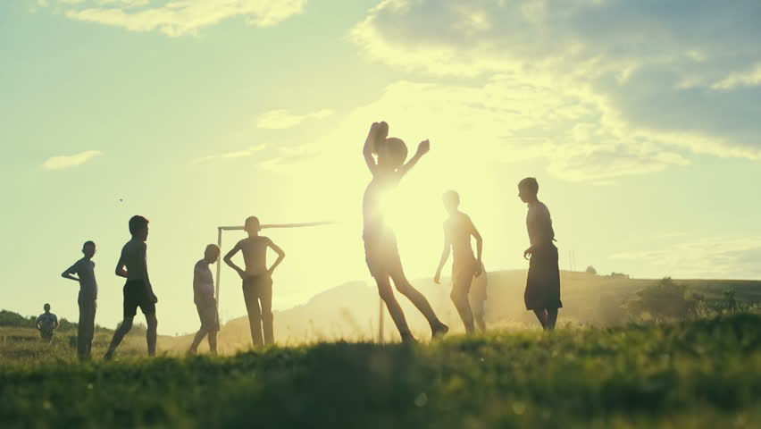 Unidentified children play football in a village on the background of sunset. Slow motion. #17646247