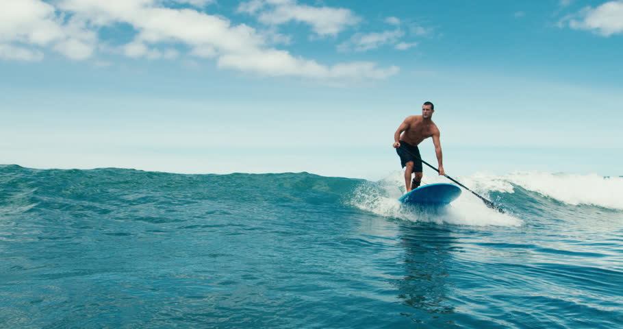 Surfer rides blue ocean wave in Maui, Hawaii in slow motion