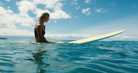 Beautiful surfer girl floating on surfboard in blue ocean