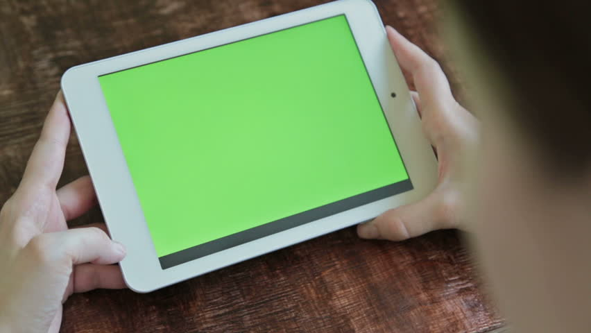 Woman sitting and looking at white digital tablet computer device with blank green display. Mock up, entertainment, copyspace, template, leisure time, chroma key, green screen, technology concept