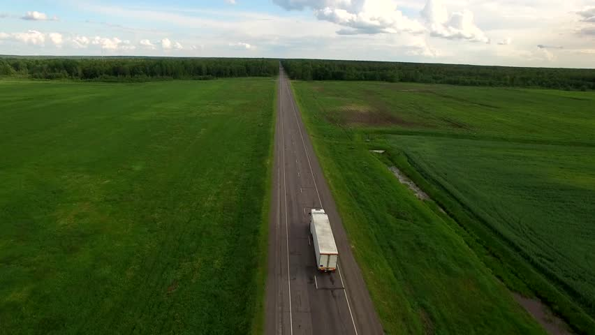 Aerial view camera flies following white cargo truck moving patched bad countryside road between green field - slow and high video footage shot with drone quad copter 4K HD