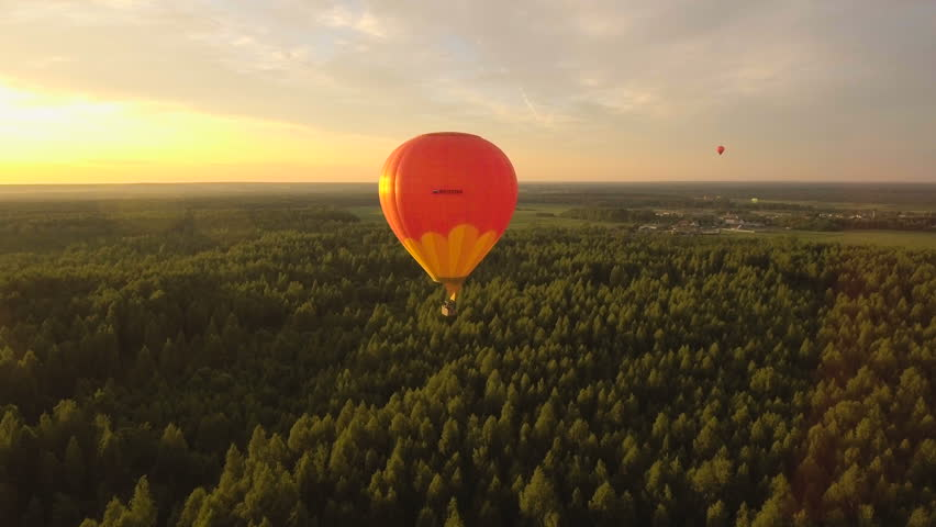 Hot air balloons in the sky over a field in the countryside.Aerial view:Hot air balloons in the sky over a field in the countryside in the beautiful sky and sunset.Aerostat fly in the countryside.