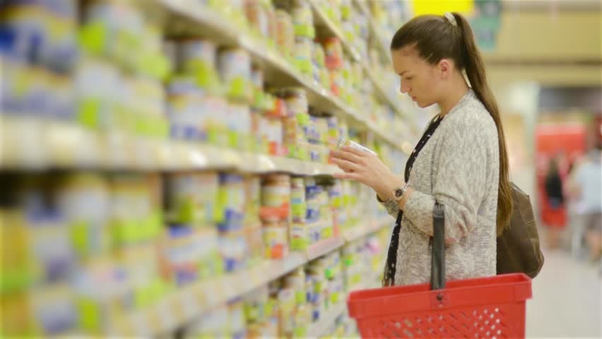 Young woman chooses baby food in the supermarket, Mother chooses food for their child in the market, girl stands near the supermarket shelf and selects the products | Shutterstock HD Video #17686009