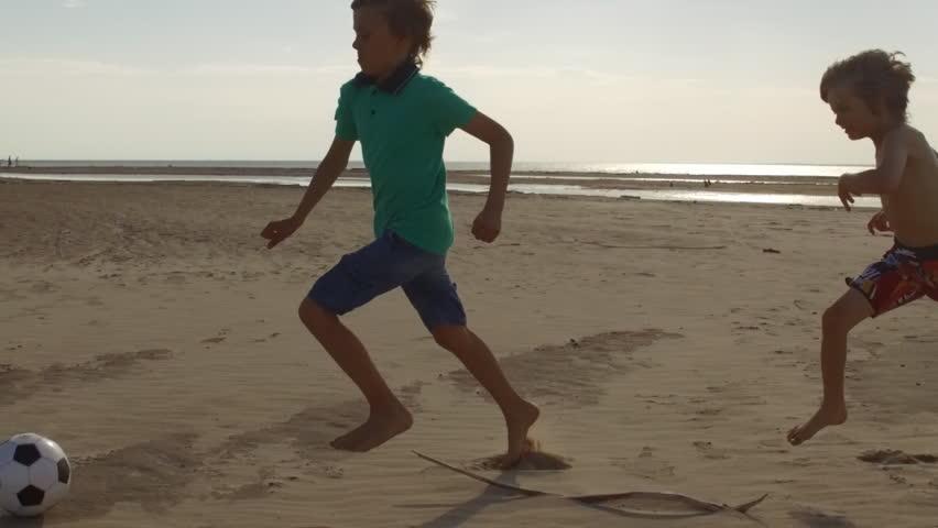 boys kicking soccer ball at beach, kids playing football slow motion