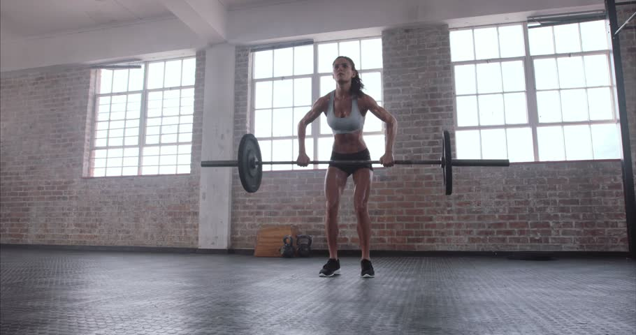 Female bodybuilder doing exercise with heavy weight bar. Full length of fitness woman practicing deadlift at health club.