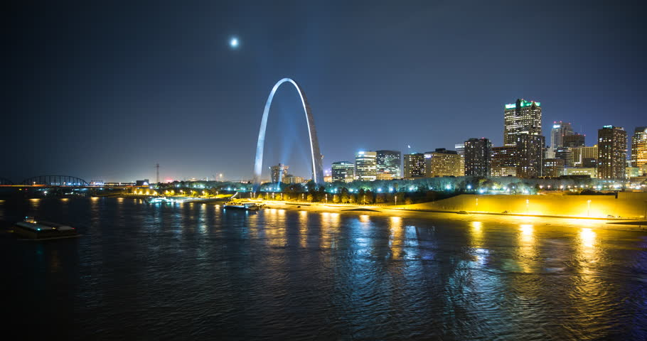 St. Louis, Missouri, USA - view of the illuminated city at night with the Gateway Arch monument and the Mississippi River with passing ship - Timelapse with zoom in - 11/14