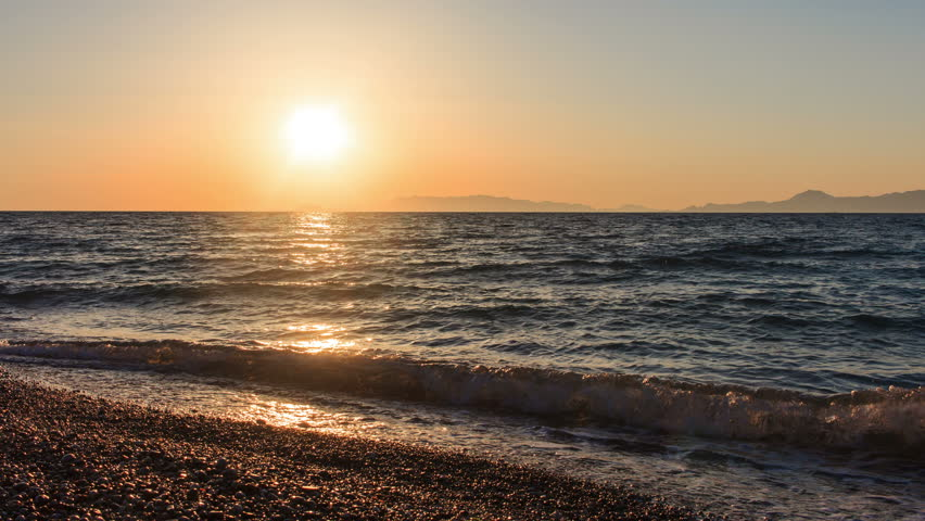 Sun sets behind horizon and the rocks in sea Greece Aegean evening | Shutterstock HD Video #17729116