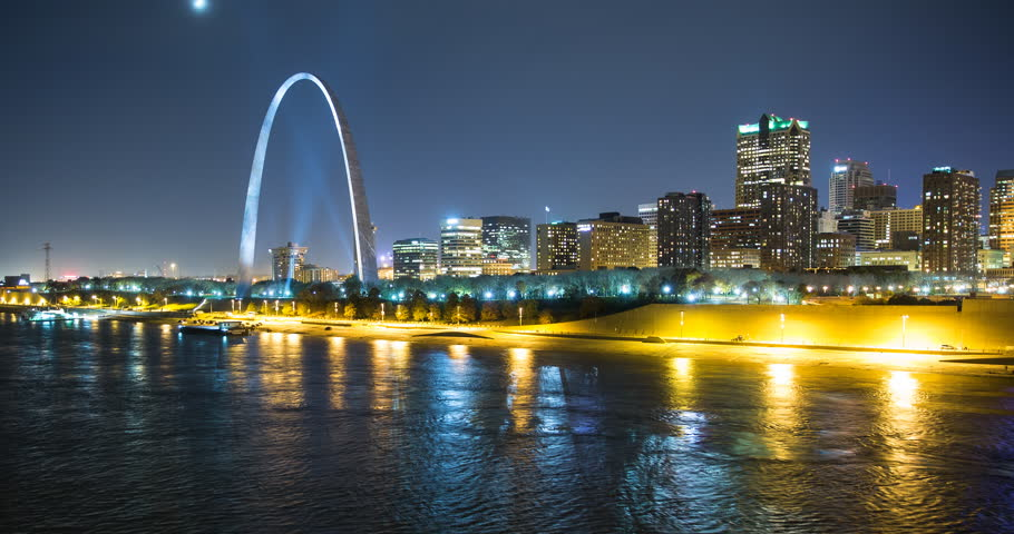 St. Louis, Missouri, USA - view of the illuminated city at night with the Gateway Arch monument and the Mississippi River with passing ship - Timelapse with pan right to left