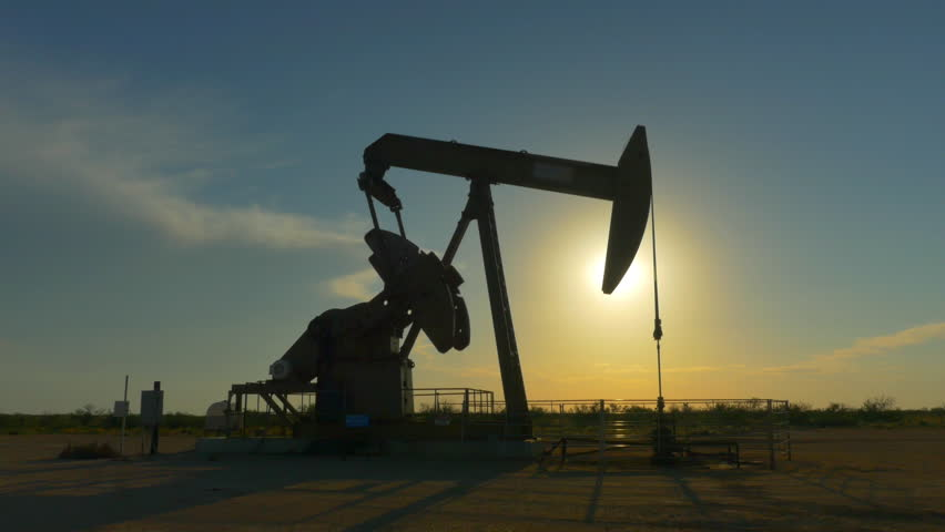 CLOSE UP: Industrial oil pump jack pumping crude oil for fossil fuel energy with drilling rig in oil field. Nodding donkey pump working over the setting sun in the middle of desert at golden sunset