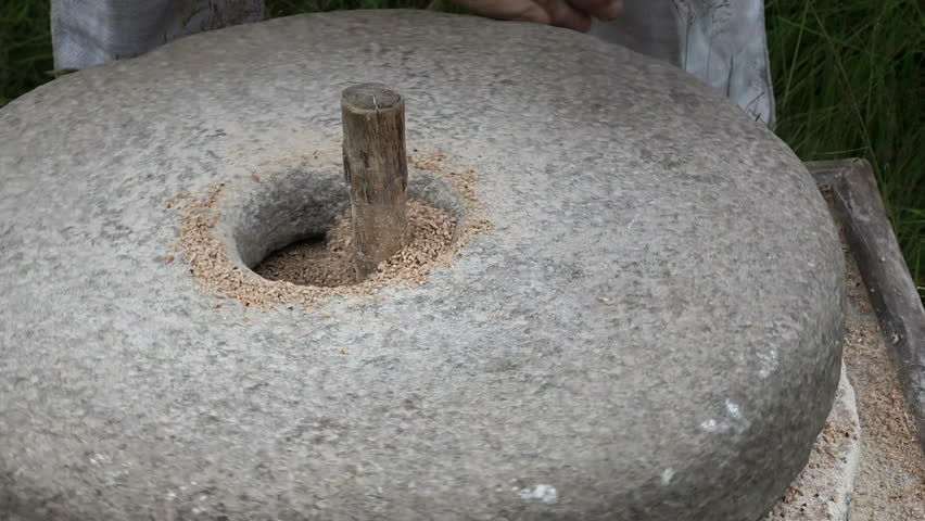 Close-up shot of historic hand-driven millstone grinding wheat