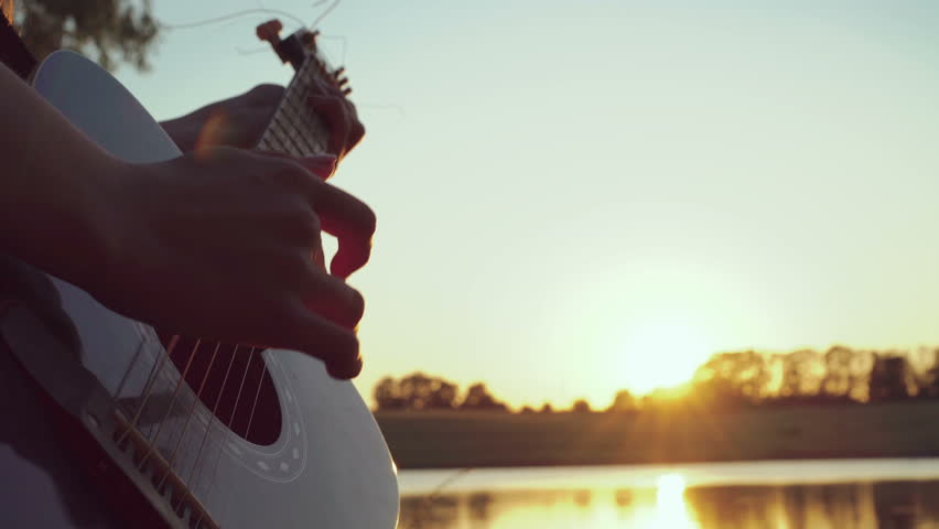 Close up of girl's hands playing guitar near the evening pond. 4k | Shutterstock HD Video #17776171