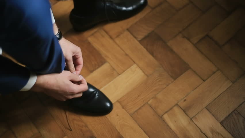 Groom is wearing shoes indoors on the white wooden background | Shutterstock HD Video #17788798