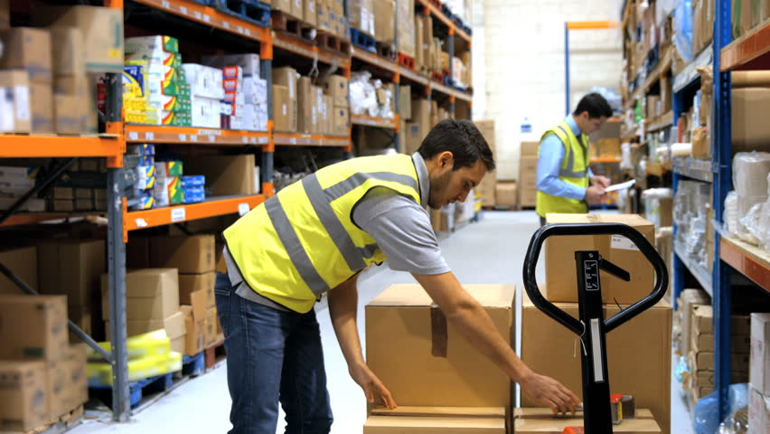 Caucasian worker with backache while lifting box in warehouse