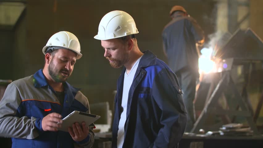 Two engineers in hardhats discussing in front of welding process Royalty-Free Stock Footage #17799112