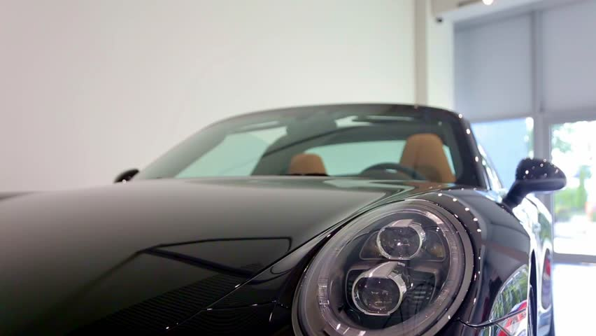 Headlight of black car, which stands in the car showroom, is flashing with bright white light. Disable of car alarm.