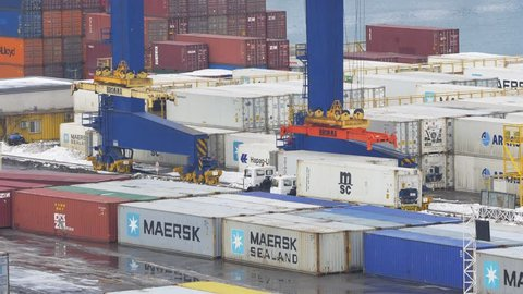 ODESSA - JANUARY 18, 2016: Unloading containers from cargo trucks with yard crane spreader in cargo terminal of trading port on January 18, 2016 in Odessa, Ukraine.