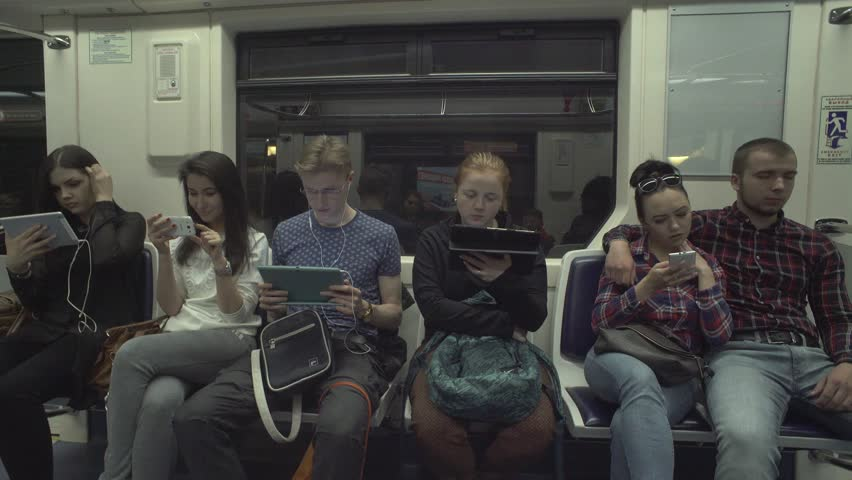 Young people reading news online, using app, texting on gadgetsin metro train