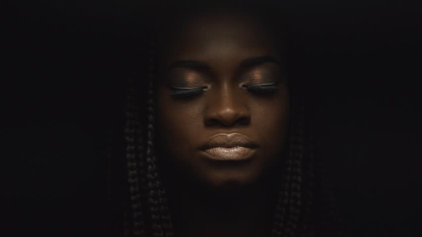 Surreal close-up portrait of young african american female model with gold glossy makeup. Face art. Fashion concept